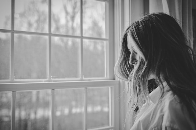 Photo of woman standing by window