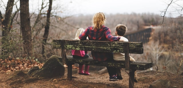 Photo of mother sitting on a bench with her children